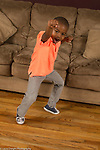 4 year old boy at home portrait active full length punching fist forward happy