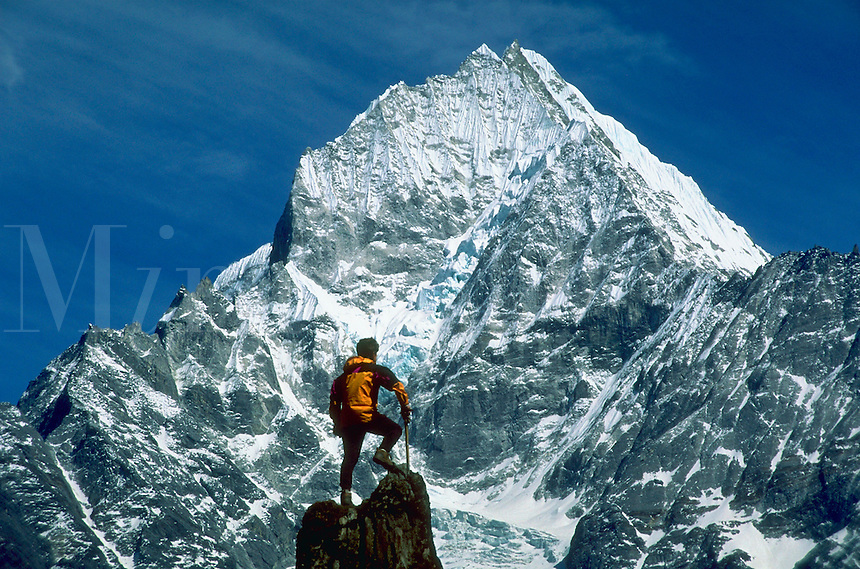 A climber on a rocky peak viewing snow covered Thamseku with blue sky in the background in the Mount Everest region of Nepal.