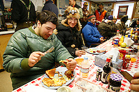 Thursday March 8, 2007   ----  Brothers Ray Redington Jr. (left) and Ryan Redington, grandsons of the Father of the Iditarod Joe Redington Sr. ,  eat a hearty breakfast made by the residents of Takotna during their 24 hour layover there.