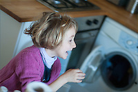 Little blond girl laughing and running around in the kitchen, France.