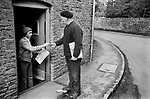 Upper Slaughter, Gloucestershire 1975. England. Postman delivery newspapers in the village.<br /> <br /> Roger Woodly in doorway.