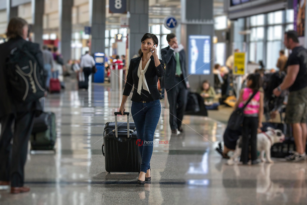 Attractive young businesswoman talks on her mobile cellphone while pulling suitcase luggage through the terminal at the Austin–Bergstrom International Airport (ABIA).