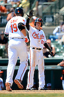 Baltimore Orioles outfielder Kyle Hudson #80 greets Chris Davis #19 after hitting a home run during a Spring Training game against the New York Mets at Ed Smith Stadium on March 30, 2013 in Sarasota, Florida.  (Mike Janes/Four Seam Images)