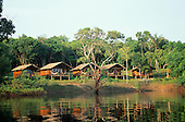 Anavilhanas, Brazil. Tourist ecolodge cabins with hammocks from across the river lagoon.