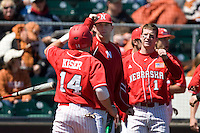 Nebraska Cornhusker Boomer Collins (1) greets teammate Kale Kiser after scoring against Texas on Sunday March 21st, 2100 at UFCU Dish-Falk Field in Austin, Texas.  (Photo by Andrew Woolley / Four Seam Images)
