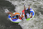 Couple in inner tubes in Confluence Park, Denver, Colorado, USA.