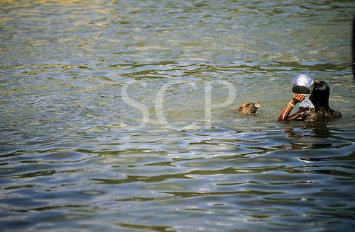 Bacaja village, Brazil. Xicrin woman washing an aluminium pot in river with a pet pig. Xicrin Indian tribe, Amazon.