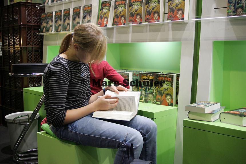 Junges Mädchen liest den neuen Harry Potter auf der Buchmesse