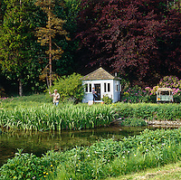 A small blue-painted clapboard fishing lodge beside a gently flowing river