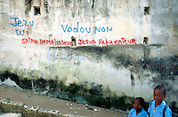 """Haiti. Province of Ouest. Port-Au-Prince. Slum of Campêche. Highly densely populated. Two brothers dressed with their blue blue uniforms on the way to school. The writing on the wall says: """" The devil destroys, Jesus Christ repairs"""" and """"Jesus Christ yes, Voodoo cult no !"""".  © 2003 Didier Ruef"""