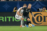 CARSON, CA - SEPTEMBER 15: Dave Romney #4 of the Los Angeles Galaxy and Johnny Russell #7 of Sporting Kansas City battle for a loose ball during a game between Sporting Kansas City and Los Angeles Galaxy at Dignity Health Sports Complex on September 15, 2019 in Carson, California.