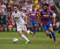 Pictured L-R: Matt Grimes of Swansea closely followed by Mile Jedinak of Crystal Palace<br />