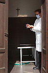 Europe Virus Outbreak - Cemetery Works in Pergine Valsugana, Italy on April 21, 2020. A sweeping lockdown is in place in Italy to try to slow down the spread of coronavirus pandemic. Employee wearing a mask wash his hands in a mortuary room.