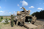 "American Sergeant Bradley Stacks throws water to a Canadian soldier from a US M3A3 Bradley vehicle in the Drawsko Pomorskie Training Area in Poland on June 10, 2015.  NATO is engaged in a multilateral training exercise ""Saber Strike,"" the first time Poland has hosted such war games, involving the militaries of Canada, Denmark, Germany, Poland, and the United States."