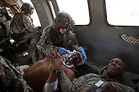 Two US Army soldiers wounded in an IED (improvised explosive device) blast console each other as they are treated on board a medevac helicopter from Charlie Company, Sixth Battalion, 101st Aviation Regiment near Kandahar. The soldier lying down on the left has severe facial wounds.