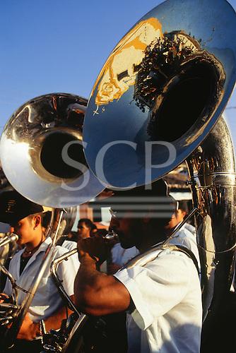 Arraial d'Ajuda, Porto Seguro, Bahia State, Brazil; Roman Catholic religious procession; tubas in brass band. Church refelcted in the tuba.