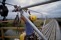 A man prepares to tighten the copper catenary cable on the overhead electrical apparatus that will provide the energy to propel electric trains across the bridge below. Construction worker. Dallas Texas USA Trinity River rail bridge.