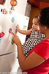 6 month old baby girl held by mother looking at objects on refrigerator language development talked to, pointing to flower magnet and naming it