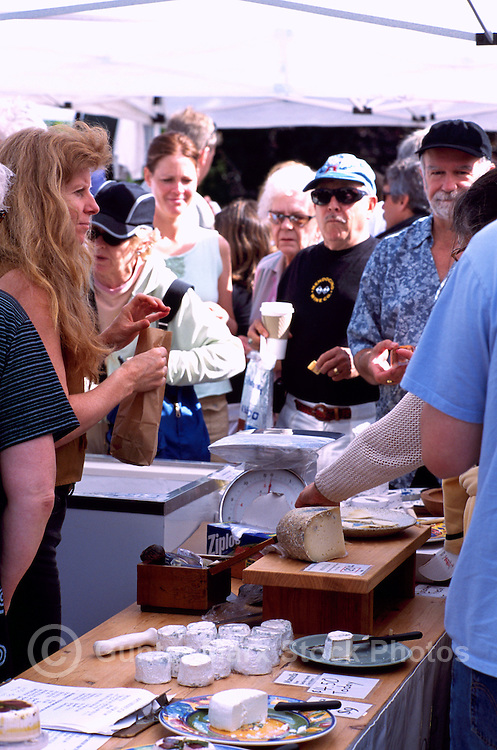 Artisan sampling and selling Cheese at the Saturday Market in Ganges, on Saltspring Island, in the Southern Gulf Islands of British Columbia, Canada