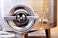 Stainless steel fermentation and storage tanks in the underground cellar. Detail of door. Kantina Miqesia or Medaur winery, Koplik. Albania, Balkan, Europe.
