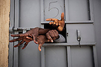 Sub-Saharan illegal migrants reach through the window of a cell in the Garabuli detention centre, pleading for water, cigarettes, food and their release. <br />