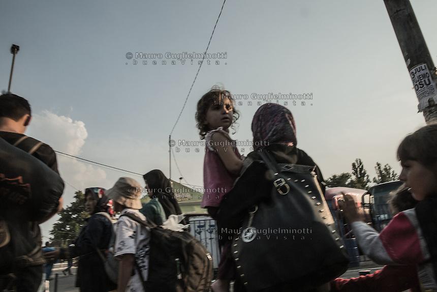 Migranti in marcia. Bambina in braccio della mamma <br /> Migrants walking. Little girl in mother's arms