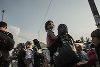 Migranti in marcia. Bambina in braccio della mamma <br />