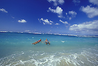 Couple swimming at remote beach at Mokuleia, North Shore of Oahu