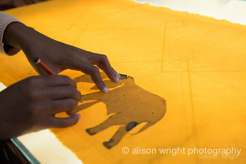 Africa, Swaziland, Malkerns.Nest organization artisan project, partnering with Baobab Batik & local artisans to help market their products to global markets and better sustain their local community. Women making batik with elephant stencil.