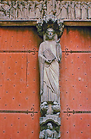 Sculpture of Jesus standing at the entrance to Chartres Cathedral with the book of life in his hand. South Porch, central bay. His feet rest on a lion and a dragon.