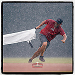 Greg Burgess, head of operations and grounds at the Greenville Drive, pulls the tarp during a sudden downpour at a game on Friday, August 3, 2018, at Fluor Field at the West End in Greenville, South Carolina. (Tom Priddy/Four Seam Images)