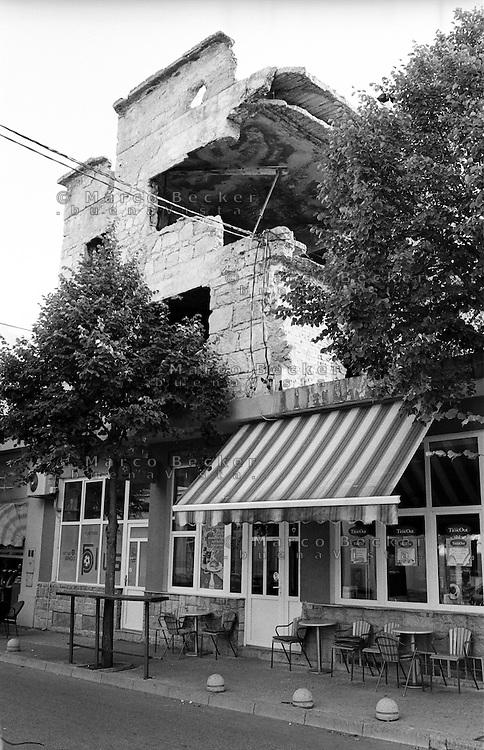 Mostar, bar e negozi al piano terra di un edificio sventrato durante la guerra --- Mostar, bars and shops on the ground floor of a building destroyed during the war