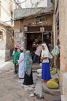 Zanzibar, Tanzania.  Stone Town Street Scene.  Jackfruit rests on the step.  Photos of Obama, the Clintons, and George Bush are posted above the door of the shop.