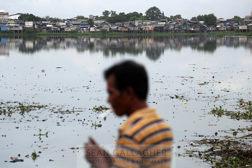 A man smoking on the banks of a reservoir in the north of Jakarta. Many of the city's poorest residents live on the banks of the city's waterways making them the most vulnerable to flooding which often ravages the city.
