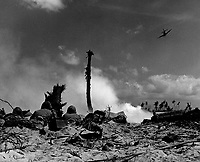 An American plane sweeps overhead to strafe the enemy hidden in their coral trenches, while a group of Marines lie prone in the sand peppering the Japs across smoking NoMan's Land with rifle fire.  Eniwetok Atoll, Marshall Islands, February 1944.  (Coast Guard)<br /> Exact Date Shot Unknown<br /> NARA FILE #:  026-G-3364<br /> WAR & CONFLICT BOOK #:  1184