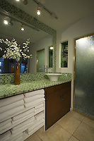 Bathroom vanity with stacked white towels are show in a mid-century home