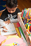 Education preschool 3-4 year olds boy writing alphabet letters on dry erase board