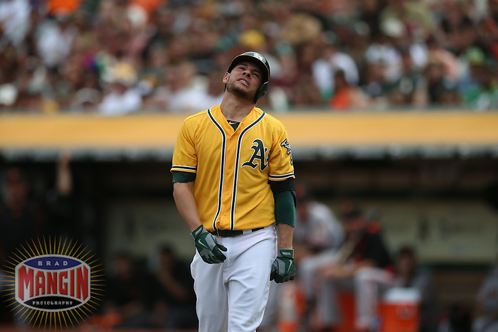 OAKLAND, CA - SEPTEMBER 27:  Danny Valencia #26 of the Oakland Athletics reacts after being hit by a pitch against the San Francisco Giants during the game at O.co Coliseum on Sunday, September 27, 2015 in Oakland, California. Photo by Brad Mangin