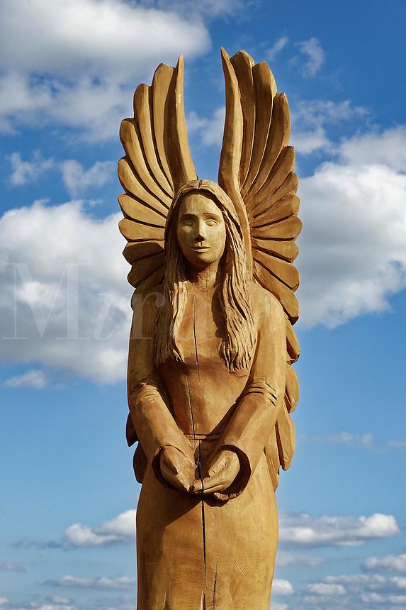 Angel wood carving against blue sky.