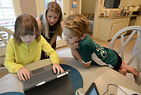 Katie Presley, 11, (from left), her mother, Jacqueline Presley, and brother, Jackson Presley , 9, look Thursday, Sept. 10, 2020, at what Katie is working on while completing school work at their dining room table in their home in Springdale. Both are enrolled in the Springdale School District's Virtual Innovation Academy in the Don Tyson School of Innovation. Visit nwaonline.com/200913Daily/ for today's photo gallery. <br /> (NWA Democrat-Gazette/Andy Shupe)