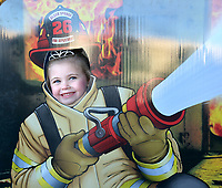 Janelle Jessen/Herald-Leader<br /> Raeylynn Robinson tries out being a firefighter during the Downtown Trick or Treat event on Thursday. Firefighters and police officers passed out candy and did activities with kids at Fire Station No. 2.