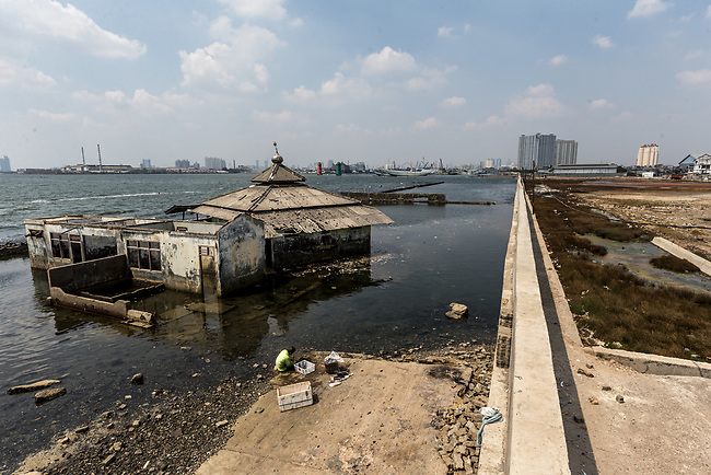 13 August 2019, Jakarta, Indonesia: A lone fisherman squats on the shore in front of a mosque that has been claimed by the sea beside the protective seawall barrier at Muara Baru, North Jakarta. Local residents were speaking about the lack of water facilities that the local poor population has access to. Water is hauled in each day by motorcycle and trucks and by hand to allow residents of the kampungs to  buy it for washing and to do laundry. Separate water is needed for drinking. The Jakarta Governor is proposing a program to send in trucks of water for the locals to get for free. They are living in villages below the seawater line on the coast of Jakarta that is sinking faster than anywhere else in the world so they have the position of being surrounded by water yet not having access to clean supplies. Picture by Graham Crouch/The Australian