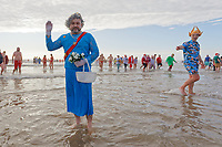 Pictured: A man dressed as The Queen takes to the sea. Wednesday 25 December 2019<br /> Re: Hundreds of people in fancy dress, have taken part in this year's Porthcawl Christmas Swim in south Wales, UK.