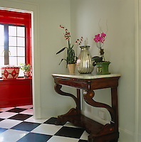 A marble-topped console table in the hall which has oversized black and white floor tiles