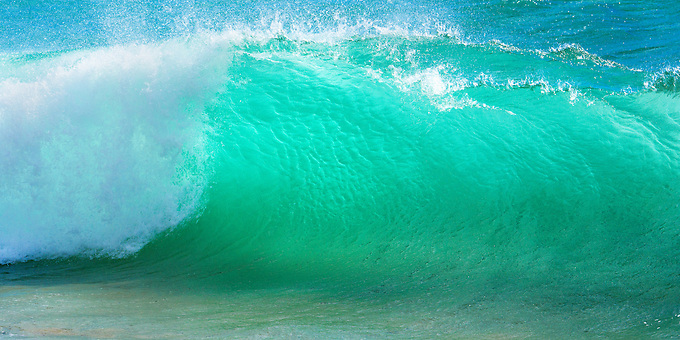 Late afternoon sun illuminates the emerald green shors of the Pacific Ocean during a summer swell.