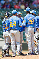 Myrtle Beach Pelicans pitching coach Steve Mintz (center) has a meeting on the mound with relief pitcher Abel De Los Santos (28) during the game against the Winston-Salem Dash at BB&T Ballpark on May 7, 2014 in Winston-Salem, North Carolina.  The Pelicans defeated the Dash 5-4 in 11 innings.  (Brian Westerholt/Four Seam Images)