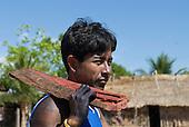 Pará State, Brazil. Aldeia Moikarako. Bepkanga Kayapo carrying a piece of Pau Brasil rosewood.