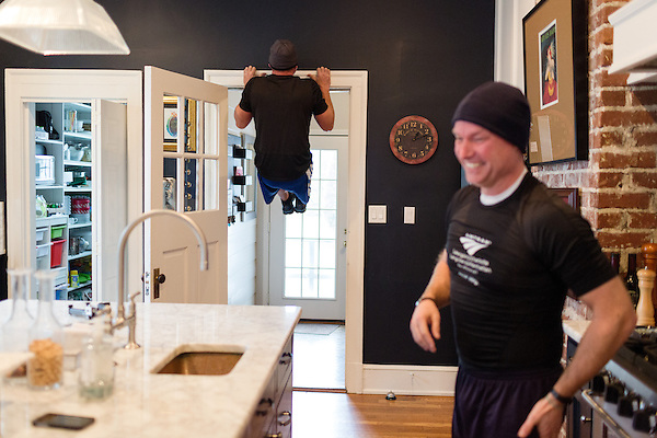 December 22, 2014. Lexington, North Carolina.<br />  Stan Lanier, Mayor Newell Clark's cousin, performs a pull up in the the Mayor's kitchen before heading out into the town for their workout.<br />   Newell Clark, the 43 year old mayor of Lexington, NC, leads a group of friends and colleagues on a 4 times a week exercise routine around downtown. The group uses existing infrastructure, such as an abandoned furniture factory, loading docks, stairs, and handrails to get fit and increase awareness of healthy lifestyles in a town more known for BBQ.<br /> Jeremy M. Lange for the Wall Street Journal<br /> Workout_Clark