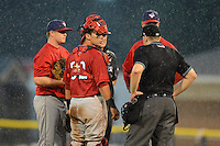 Auburn Doubledays pitcher Mike Mudron #29, catcher Erick Fernandez #32, and manager Gary Cathcart #24 talk with umpires Dave Attridge and Nate Caldwell before a rain delay during a game against the Batavia Muckdogs on July 3, 2013 at Dwyer Stadium in Batavia, New York.  Batavia defeated Auburn 12-2.  (Mike Janes/Four Seam Images)
