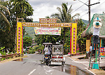 """The town's welcome sign is decorated with colorful greetings banners, welcoming visitors to Sampaloc's Bulihan Fiesta in April 2012.  Meanwhile, workers decorate lampposts along the road with buri """"hats"""" for the festival."""